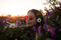 Artistic portrait of woman in red glasses among flowers
