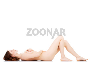 Sexy fit naked woman with healthy clean skin lying down