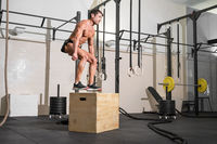 Full shot of a fit young caucasian sportsman training alone doing box jump exercise in the gym.