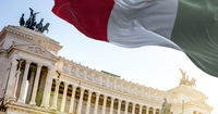 The Italian flag waving in the wind with Vittoriano in Rome in the background