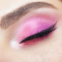 Closeup macro shot of closed human female eye. Girl with perfect skin and pink eyes shadows