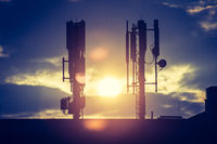 5g and communication tower: Silhouette of communication tower on rooftop, evening