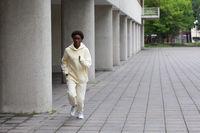 African American runner woman in hoodie jogging outdoors