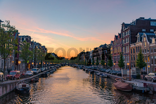 Buildings and boats along the canal at sunset time in Amsterdam, Netherlands