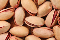 Tabletop view, closeup of turkish red pistachios on wooden board.