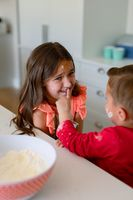 Portrait of happy, dirty with dough caucasian siblings baking in kitchen