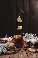 Christmas cup of Mulled Wine on table, levitating cinnamon stick, orange, apple