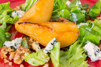Salad with caramelised pears,walnuts and blue cheese, on red plate