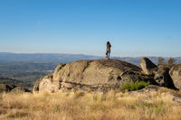 Caucasian young woman with brown dog on top of a boulder stone seeing Sortelha nature mountain landscape, in Portugal