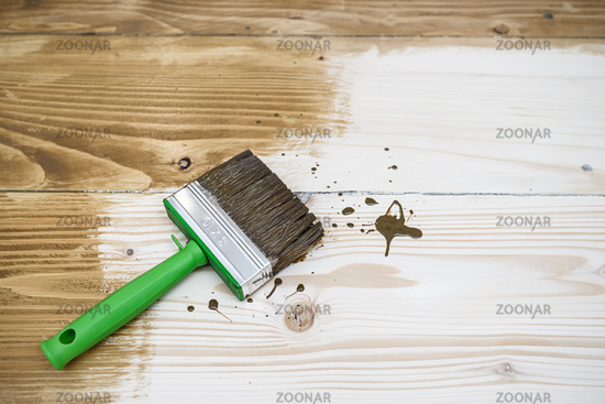 Square cut brush on wooden floor made with softwood boards. Toning floor with wood stain, emphasizing the texture. Decoration process. Stage before varnishing
