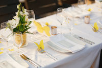 Wedding dinner table reception. Glass transparent bath with sliced lemons and a bouquet of white Alstromeri, on the table against the background of the glare of water in the sunset light