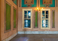 Wooden windows with green shutters, green frames with ornate border, and tiled marble floor