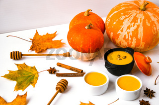 Autumn food. Pumpkin puree soup, leaves. Autumn harvest, pumpkins, leaves on grey as abstract background. Thanksgiving day.