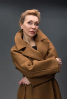 full length portrait of a fashionable aged woman isolated on grey