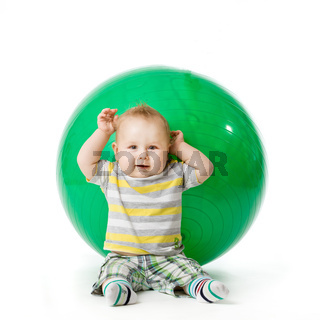 sweet small baby with fitness ball on a white background.