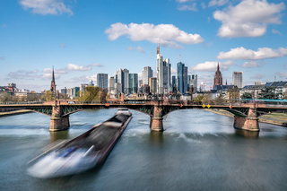 Frankfurt, Germany - March 31, 2020: frankfurt skyline view with a cargo ship passing underneath ignas bubis bridge