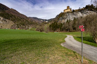 view of the Ortenstein Castle in the Swiss Alps with a hike and bike trail in the foreground