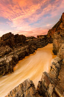 Water rushes up a sloping rocky embankment on the beach