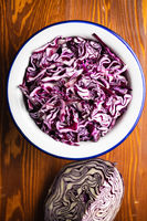 Sliced fresh red cabbage in bowl on wooden table.