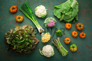 Assortment of organic vegetables on green background.