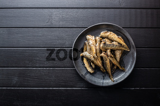 Smoked sprats on plate. Canned sea fish