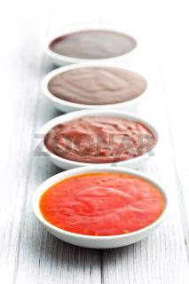 various barbecue sauces in ceramic bowls