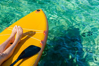 stand up paddle board with visible legs of a young girl and a paddle on the turquoise surface of the ocean