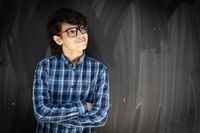 Teenage boy with glasses in front of classroom board