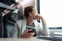 Thoughtful businesswoman listening to podcast on mobile phone while traveling by train.