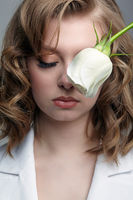 Woman in white jacket with eyes closed and with white rose flower near face.