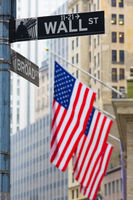 Wall street sign in New York with American flags and New York Stock Exchange in background