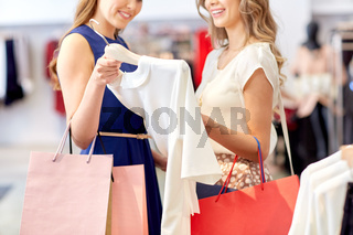 happy women with shopping bags at clothing shop