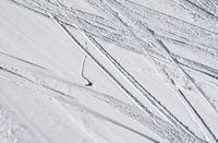 Groomed snowy ski slope with trace from skis, snowboards and stone at winter