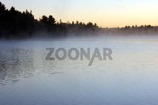 Sunrise and mist in beautiful lake in Algonquin Park