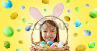 happy girl with colored easter eggs on yellow
