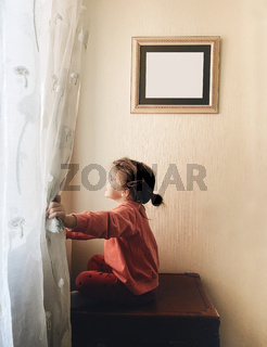 Cute adorable little girl sitting by window and smiling happily while spending leisure time at home