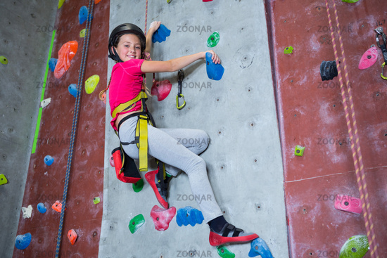 Portrait of confident teenage girl practicing rock climbing