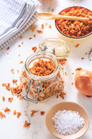 Making homemade fried onions with ingredients on white kitchen table