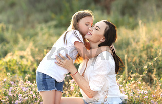 Cheerful woman with girl in field