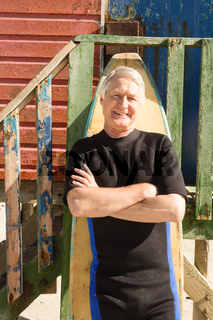 Portrait of smiling senior man standing by surfboard