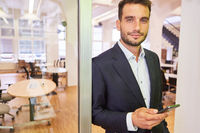 Start-Up Entrepreneur mit einem Smartphone im Büro