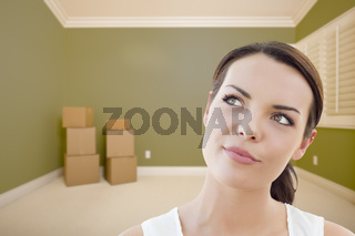 Young Woman Daydreaming in Empty Room with Boxes