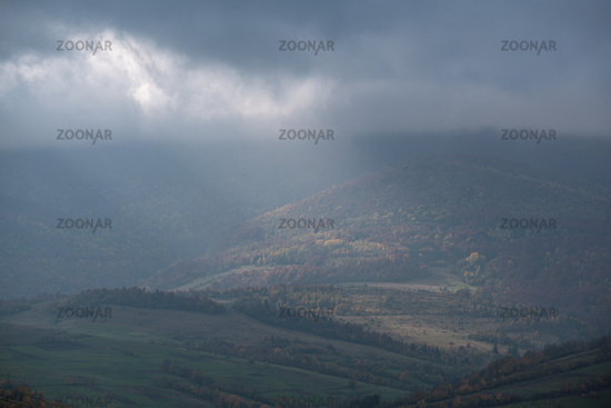 Morning foggy clouds in sunlight and autumn mountain countryside.  Ukraine, Carpathian Mountains, Borzhava Range, Transcarpathia.