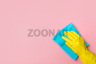 Hand in glove on pink background. Cleaning concept
