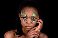 Gems in face of beautiful black woman