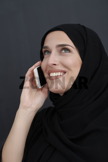 Young muslim businesswoman in traditional clothes or abaya talking on the smartphone