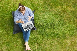 Frau am Laptop PC bei Videokonferenz auf dem Rasen