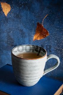 Autumn mood. Books, tea, falling autumn leaves, rain