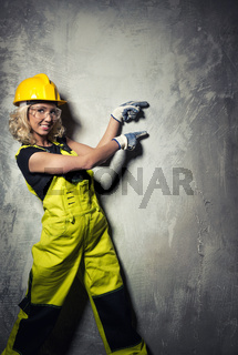 Attractive builder woman showing something with the hands, studio shot