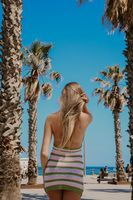 Vertical image from back of long-haired girl walking on the beach in sunny day.